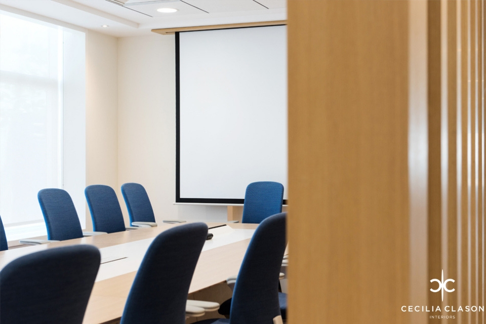 Office Interior Design - Office seen past wooden folding door, boardroom table with blue chairs and projector screene chairs and projector screen