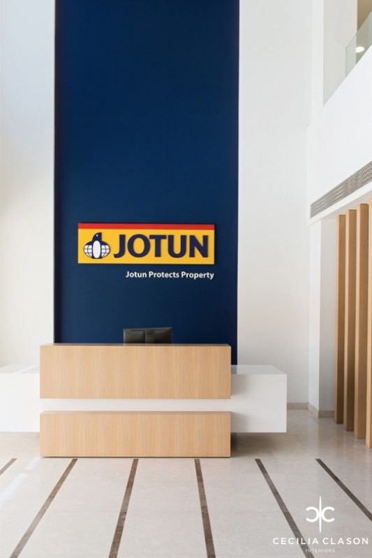 Office Reception Design - White desk with wooden partition & deep blue wall, with Jogun logo behind it & folding doors