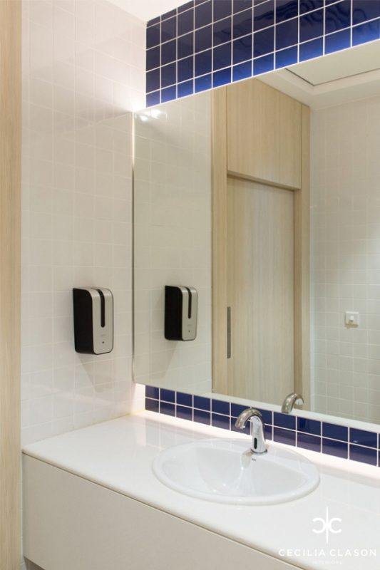 Office Bathroom Design | White tiled walls & deep blue tiles around mirror with white granite top bathroom counter