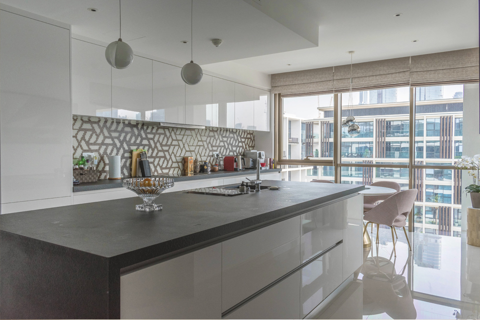 Kitchen Interior Design - Ball pendant lighting above granite kitchen counter with modern wall backdrop & large window panes