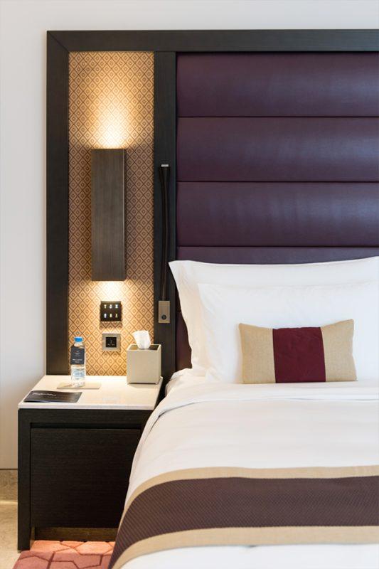 Hotel Bedroom Design - Padded velvet purple headboard & dark wood pedestal below lighting feature