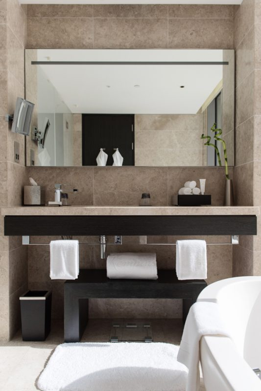 Bathroom Interior Design - Textured, tiled walls & countertop with dark, solid wood furniture next to frosted glass door