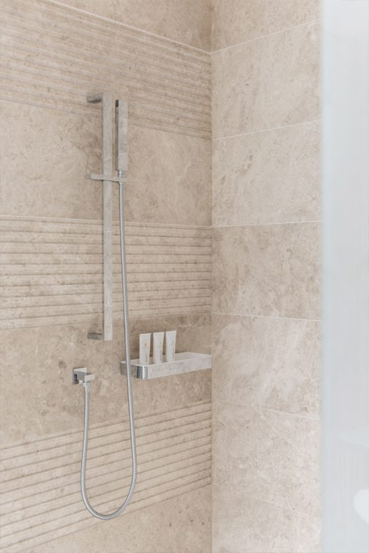 Hotel Bathroom Interior Design - Shower interior design with modern silver shower column, and patterned & tiled marble walls