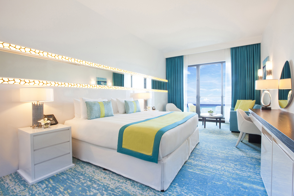Hotel Design - White furniture on laminated blue & white textured floor with matching blue curtains & patterned wall lighting