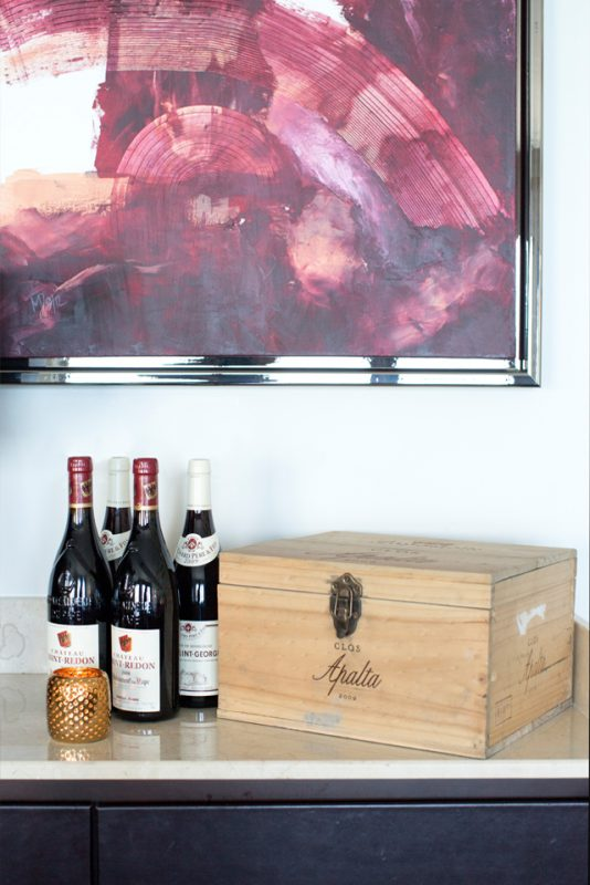 Office Interiors - Abstract wall art with gold candle holder next to wine and wooden wine box on granite counter top