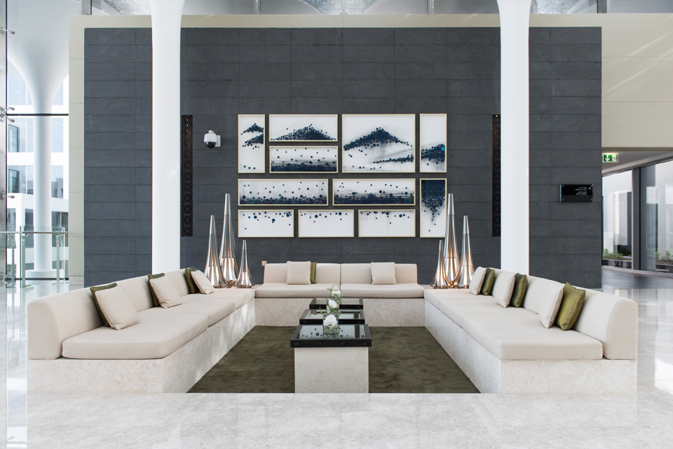 Living Room Design - White leather couches with marble floors, grey feature wall with hanging wall art & white pillars