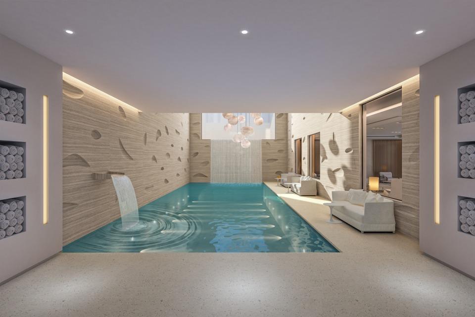 Interior Pool Design - Semi-geometric wall design next to pool, modern wall fountain & built in towel storage