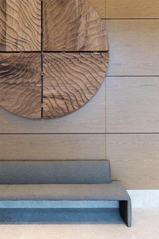 Lobby Interior Design - Large circular wooden wall art feature against wood paneled wall with modern seating