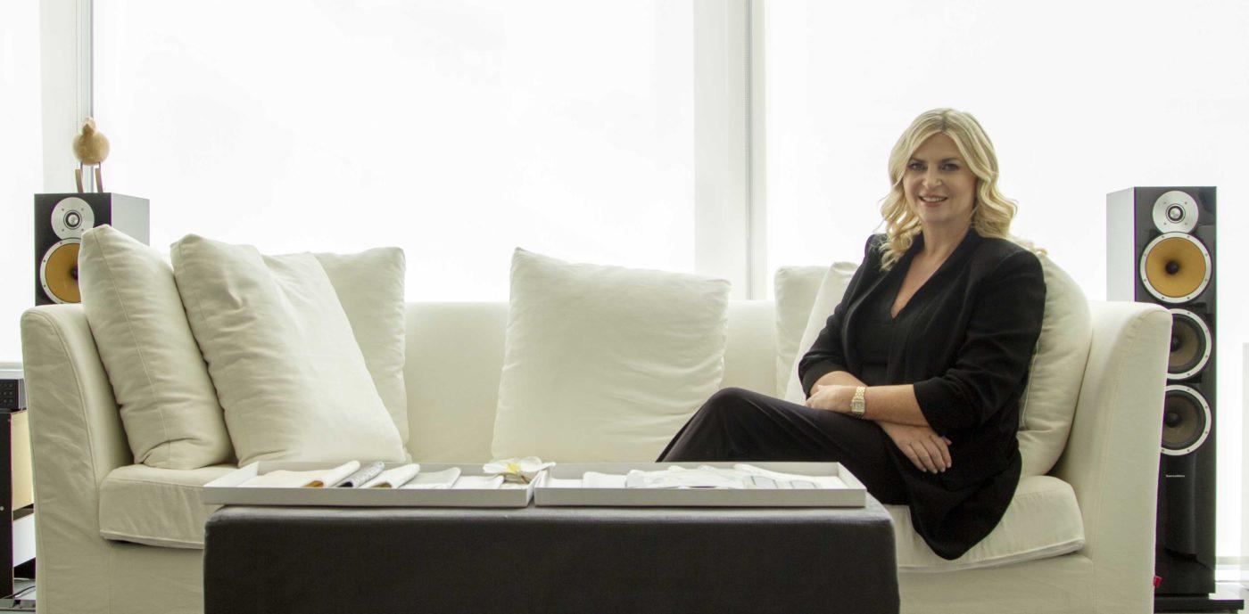 Photo of Interior Designer, Cecilia Clason sitting on a white sofa