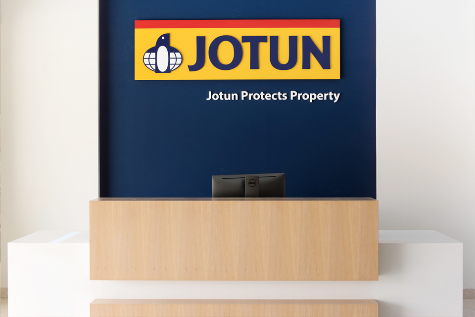 Commercial Office Reception Design - White desk with wooden partition and Jotun logo on dark blue wall