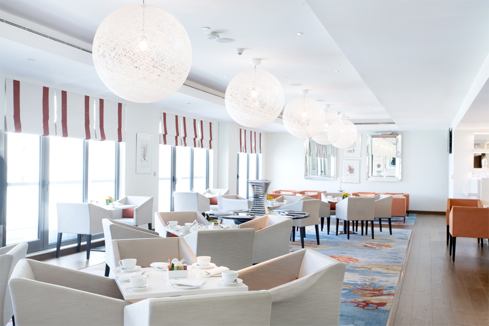 Business Lounge Design - Luxury chairs & tables on large abstract rug below white netted ball lighting