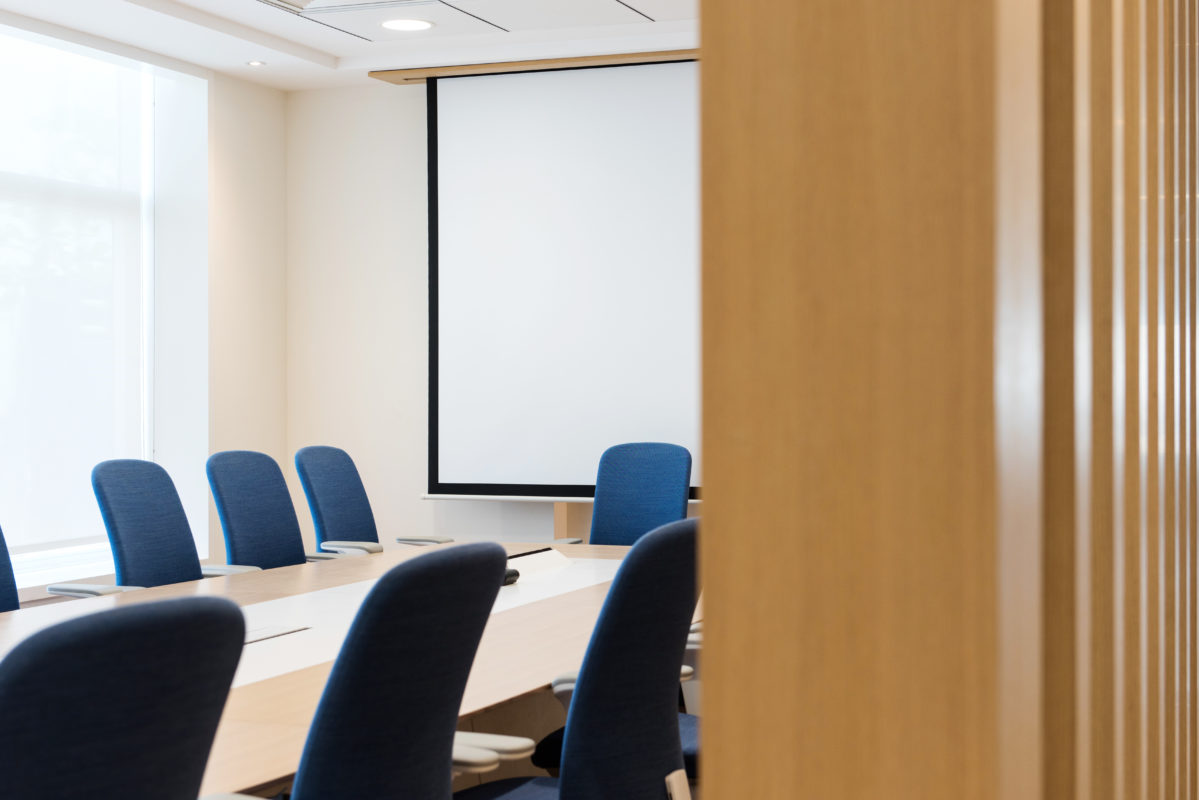 Boardroom Design - Boardroom seen past wooden folding door, boardroom table with blue chairs and projector screen