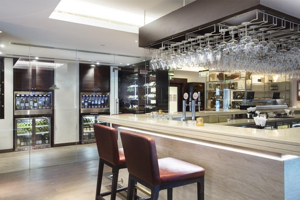 Bar Interior Design - White granite bar counter top with dark wood overbar glass rack, leather bar stools & glass wine cellar
