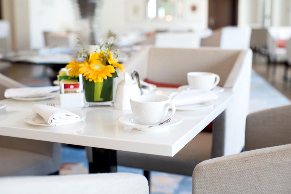 Restaurant Interior Design - Table spread with coffee cups & flower centerpiece