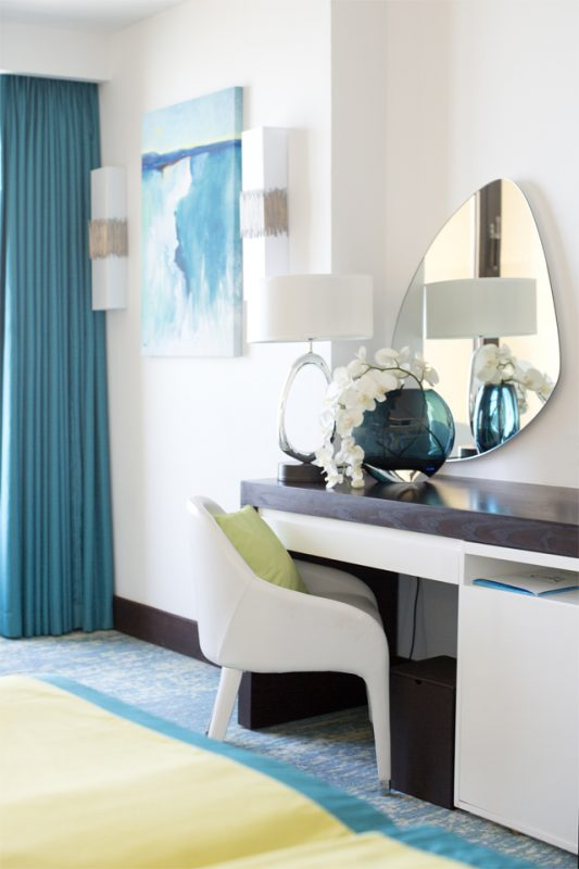 Bedroom Interior Styling - Modern white & dark wood furniture with shaped mirror & wall art matching blue curtains