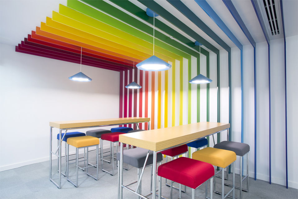 Office Cafeteria Design - Rainbow wall slats extending to roof, with colorful seating, wooden table tops & funky lighting