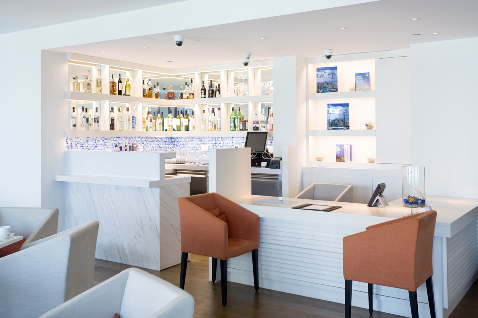 Executive Bar Interior Design - White slated & marble bar counter with built in shelving & artwork & mirrored shelving