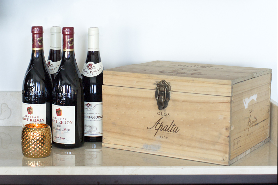 Wine Bar Decorating - Vintage wine next to wooden cigar box & gold candle holder