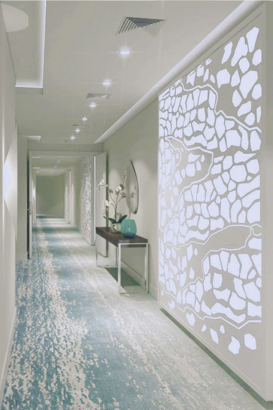 Hotel Passage Interior Design - Lighting feature on wall with textured blue & white floor below ceiling lights